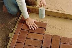 Теперь можно укладывать и саму брусчатку. Как и прежде, между плитками необходимо оставлять небольшие зазоры. Швы заделываются с помощью жидкого раствора.