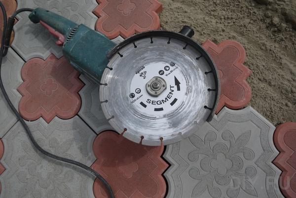 Где нужно подрезать, определяют по месту. Подрезка плитки производится с помощью болгарки с алмазным диском по бетону.