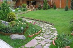 Дорожка из плитняка с проросшей травой между камнями