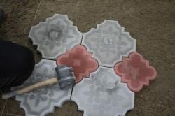 Укладка плитки с помощью резинового молотка.