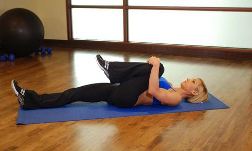Для вытягивания позвоночника нужно лечь на спину, обхватить правое колено руками и медленно притянуть ногу к груди